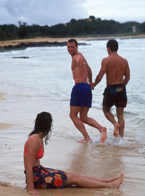 gay couple holding hands past a woman sitting on the beach